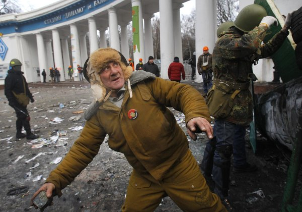 Image: An elderly protester prepares to throw a stone, during clashes with police, in central Kiev