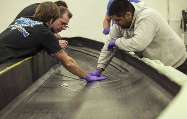 Image: Engineers apply layers of woven carbon fiber material to build a wing component of the next SpaceShipTwo craft at Virgin Galactic.