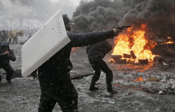 Image: A protester points a handgun during a clash with police in central Kiev, Ukraine
