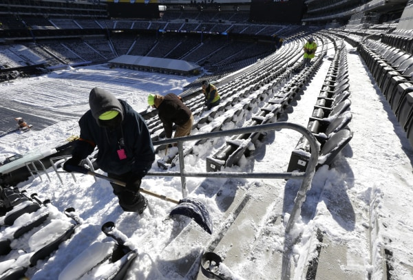 Image: Workers shovel snow off seating area at MetLife Stadium