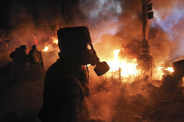 Image: Anti-government protesters gather at a barricade at the site of clashes with riot police in Kiev