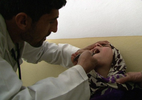 Image: Twelve-year-old Khorshid has her tooth extracted with a pair of pliers.