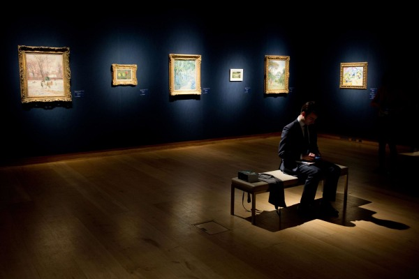 """Image: A man sits among various artworks during a press call on January 30, 2014, for the """"Impressionist, Modern and Surrealist Art"""" sale"""