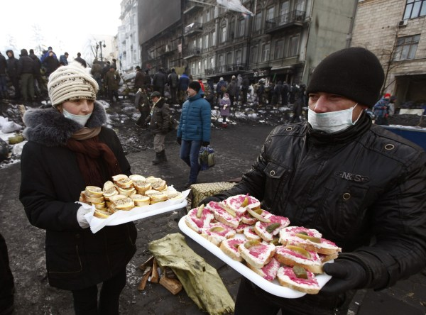 Image: Volunteers distribute sandwiches among the anti-government protesters near a barricade at the site of clashes with riot police in Kiev