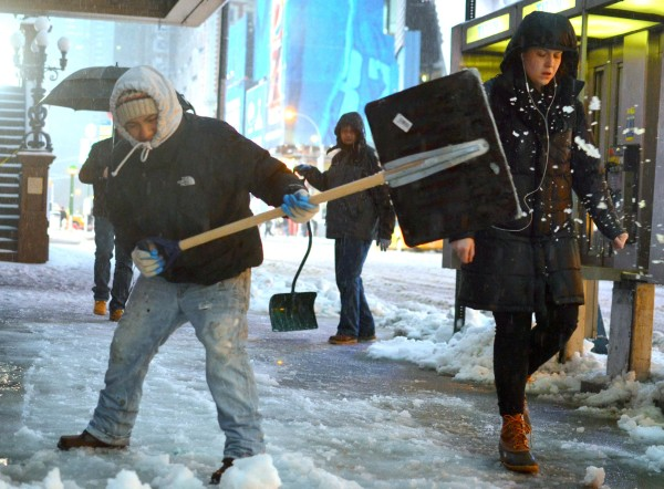A worker attempts to keep the sidewalks clear near Times Square in New York City as the Northeast continues to get hit with a wintry mix on Wednesday.