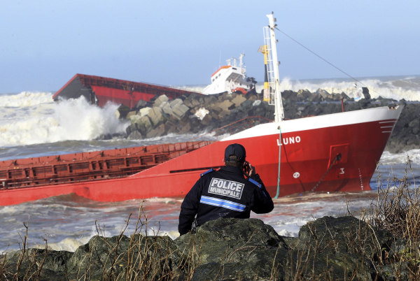 Image: A police officer watches a Spanish cargo ship that slammed into a jetty