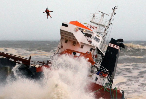 Image: A helicopter lowers a rescue worker toward Spanish cargo ship The Luno which slammed into a jetty