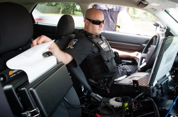 Image: Officer Jeff Innocenti, pulls a ticket from his printer, during a traffic stop