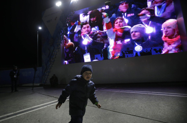 Image: People gather to watch the live telecast of the 2014 Winter Olympics opening ceremony