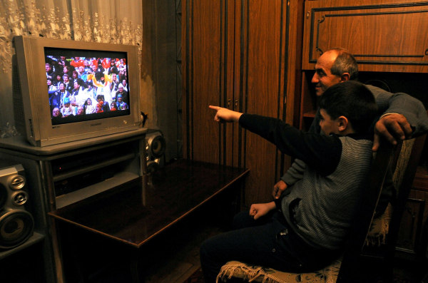 Image: People watch the television broadcast of the Opening Ceremony