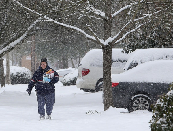 Image: Postal employee Lisa Calloway trudges through the snow as she delivers mail in Eugene, Ore. on Friday, Feb. 7, 2014.