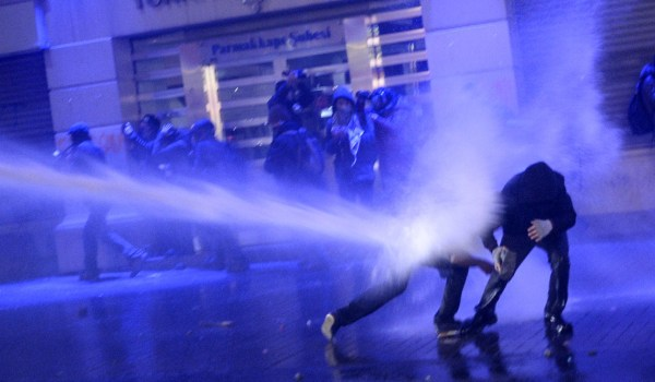 Image: Protesters are hit by water cannons