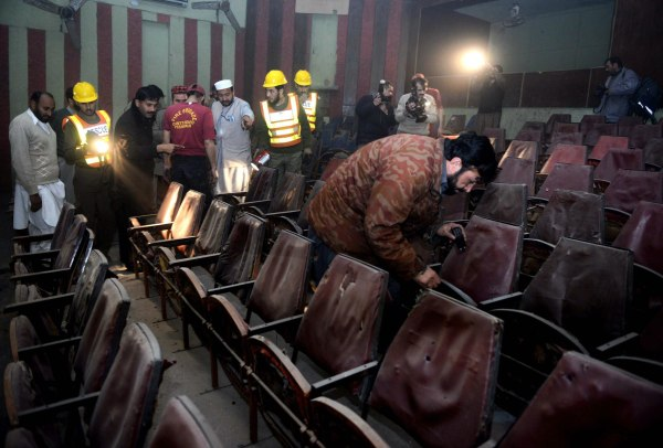 Image: Pakistani volunteers search a cinema hall after a grenade attack