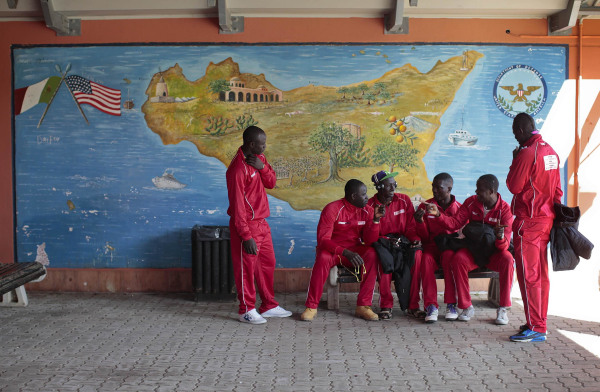 Image: African migrants, who are members of the ASD Mineo soccer team, talk as they wait to go to their Sunday match, in the immigration centre near the Sicilian village of Mineo