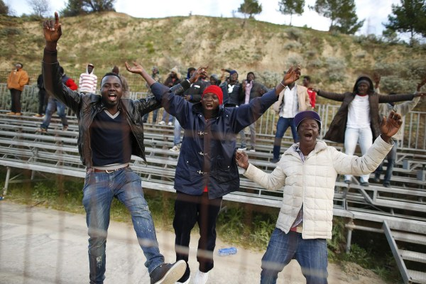 Image: African migrants, who are supporters of the ASD Mineo soccer team, celebrate after a goal in the Sicilian village of Mineo