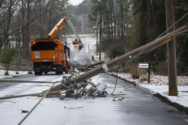 Image: Workers remove trees and snapped power poles brought down in the road in Doraville, Ga.