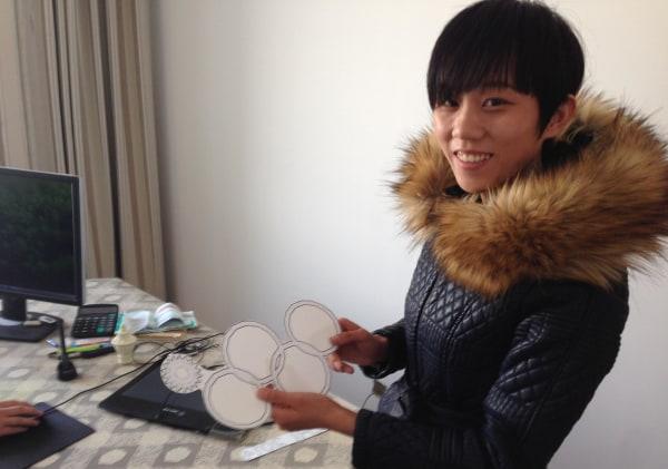 Yan Wenjuan helps her partner Zhang Zhen to print T-shirts that cash in on the Sochi Olympic rings glitch.