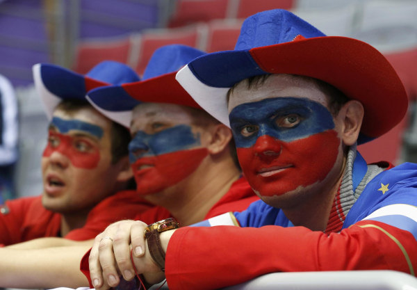Image: Fans with their faces painted in the colours of the Russian flag look on before the men's preliminary round ice hockey game between Russia and USA at the Sochi 2014 Winter Olympic Games
