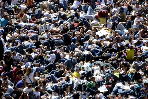 Image: Thousand of anti-government students lie on the ground during a protest in Caracas