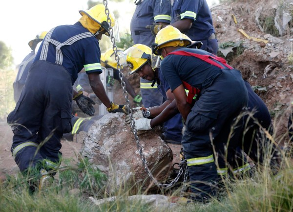 Image: Rescue officials move a rock removed from an abandoned gold shaft as they work to rescue trapped suspected illegal miners in Benoni