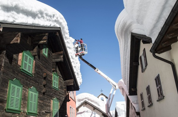 Image: Municipal workers clear snow off buildings in the village of Bedretto in Ticino, Switzerland.