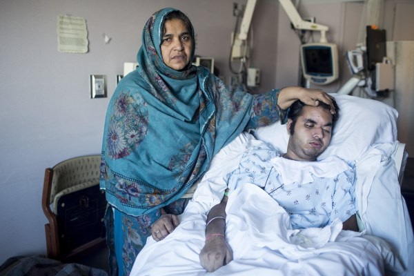 Tanzeela Bajwa stands by the side of her son, Muhammad, who lies comatose in a hospital bed at St. Mary's Medical Center in Duluth, Minn.