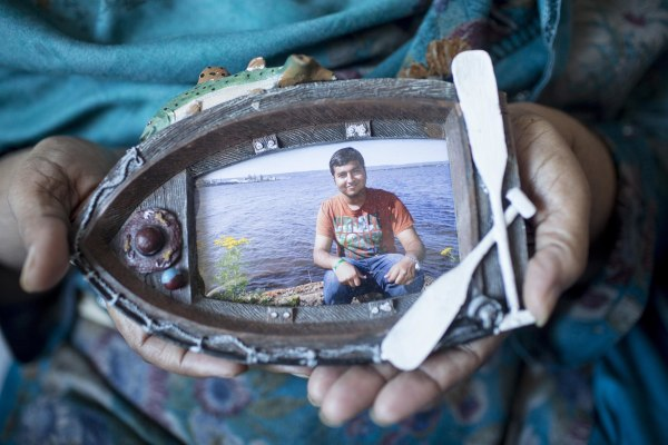Image: Tanzeela Bajwa holds a photo of her son, Muhammad, who lies comatose in a hospital bed.