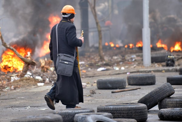Image: An Orthodox priest walks under fire during clashes between anti-government protesters and riot police in central Kiev