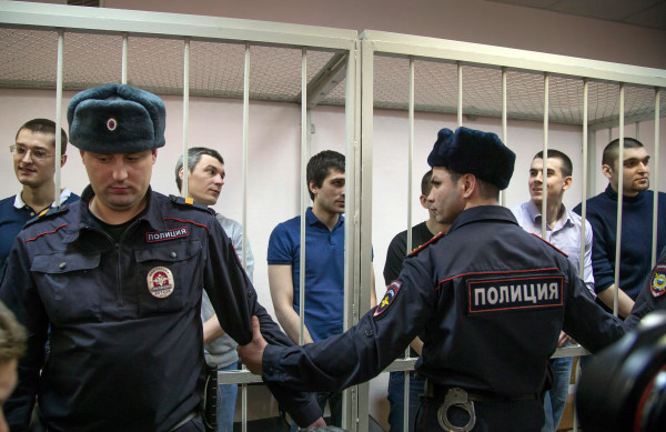 Image: Defendants stand in a glass cage during a trial in Zamoskvoretsky District Court in Moscow