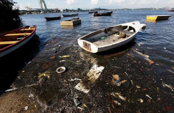 Image: Boats float along the shoreline of the polluted waters of Guanabara Bay in Rio de Janeiro