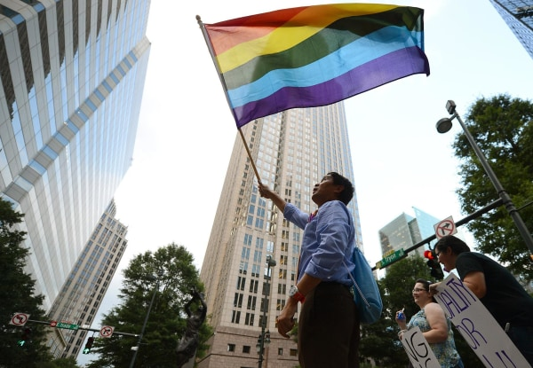 Image: A man waves a flag in Charlotte, N.C.