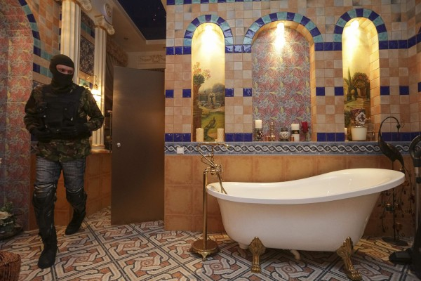 Image: A man walks past a bath tub in the house of Ukraine's former prosecutor general Pshonka in the village of Gorenichy outside Kiev
