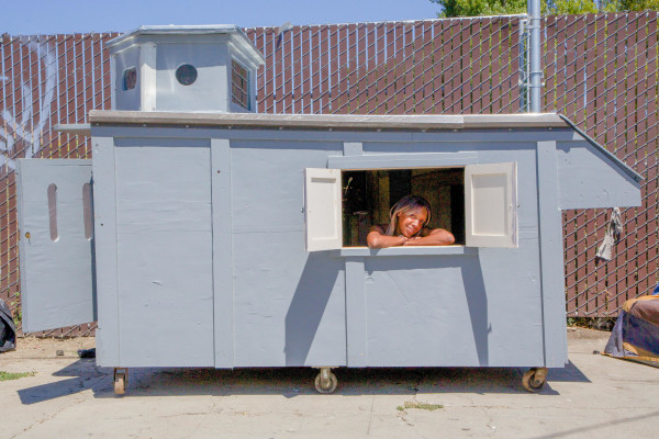 A woman is seen in a shelter built by California artist Gregory Kloehn.