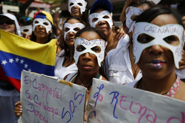 Image: Opposition demonstrators wearing carnival masks take part in a women's rally against Nicolas Maduro