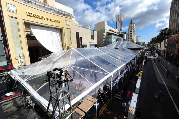 Image: A giant tarp provides the cover for expected rain as preparations continue on a covered-up Red Carpet along Hollywood Boulevard