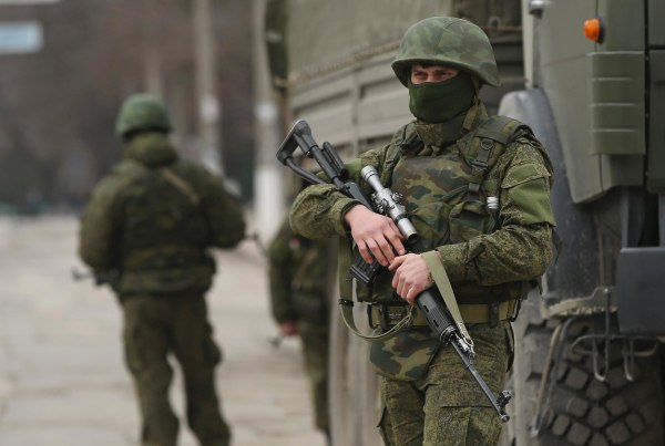 Image: Heavily-armed soldiers displaying no identifying insignia maintain watch in a street in the city center on March 1, 2014 in Simferopol, Ukraine.
