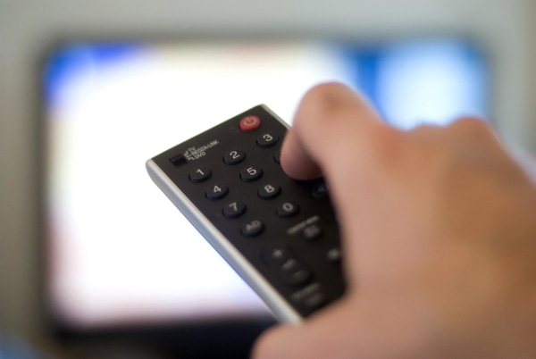 Image: A person points a remote control at a television