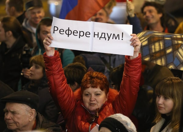 """Image: Pro-Russian sympathizers, including one woman holding a sign that says """"Referendum"""""""