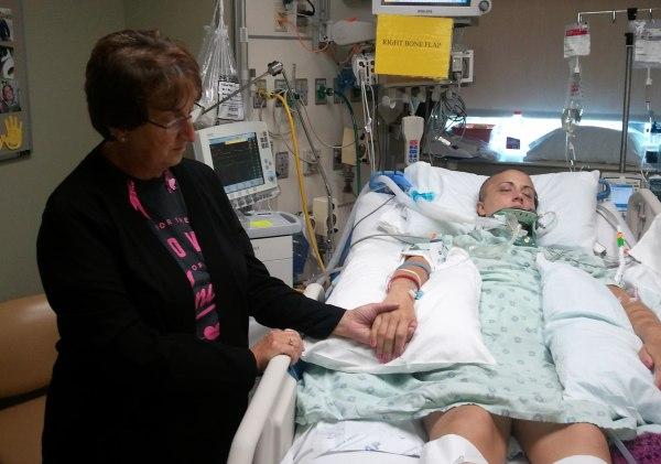 Andrea Vellinga's mother Sandi Voss holds Andrea's hand in the hospital.