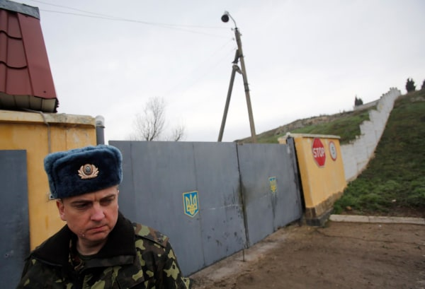 Image: A Ukrainian officer stands outside the gate of a military base at the Black Sea port of Sevastopol in Crimea