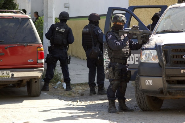 Image: Federal police stand guard during 2010 raid where security forces fought cartel members.