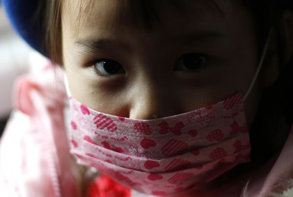 Image: A girl wearing a mask sits in a school bus heading to the Emporium kindergarten in Koriyama