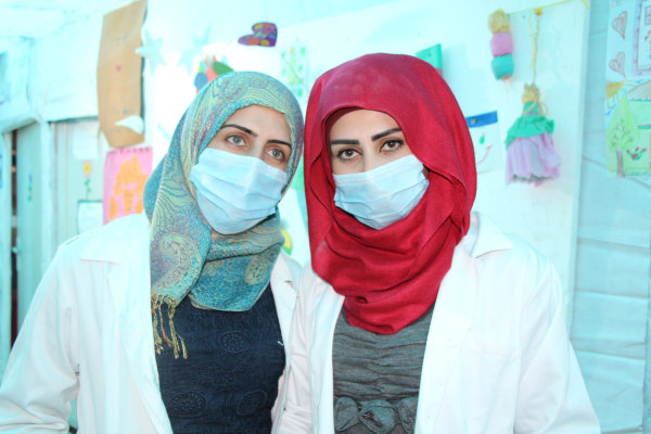 Image: Midwives provide prenatal vitamins to pregnant women in refugee camp