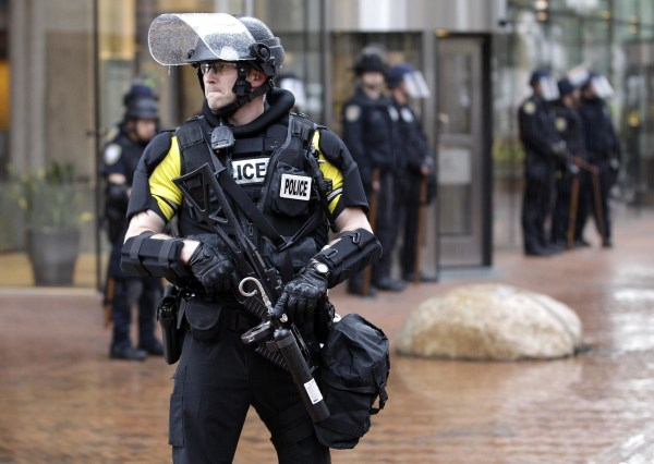 Image: A police officer armed with riot gear stands guard.