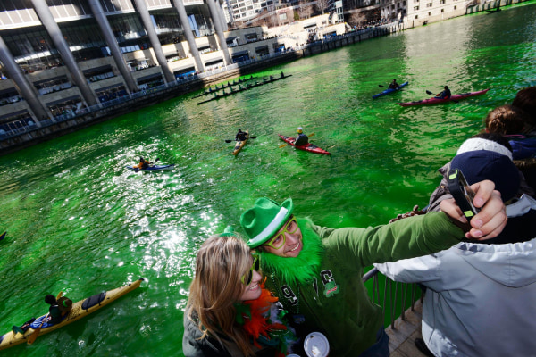 Image: People photograph themselves with a smartphone after the Chicago River was dyed green ahead of the St. Patrick's Day parade in Chicago