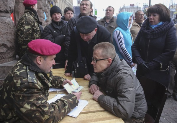 Image: A volunteer speaks with a Ukrainian military officer as he registers for service in the newly-created National Guard in central Kiev