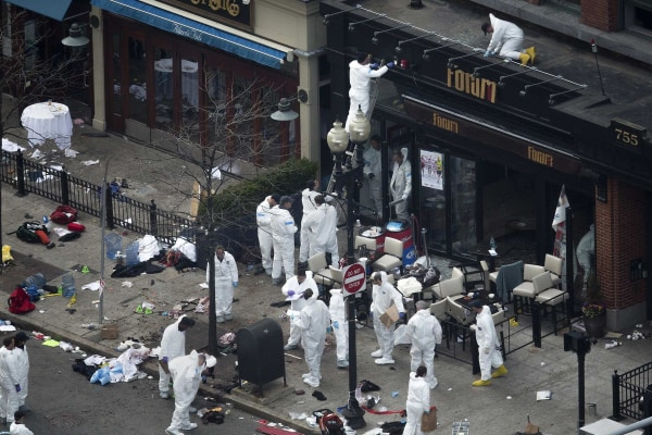 Image: Officials take crime scene photos in front of the damaged Forum restaurant a day after two explosions hit the Boston Marathon