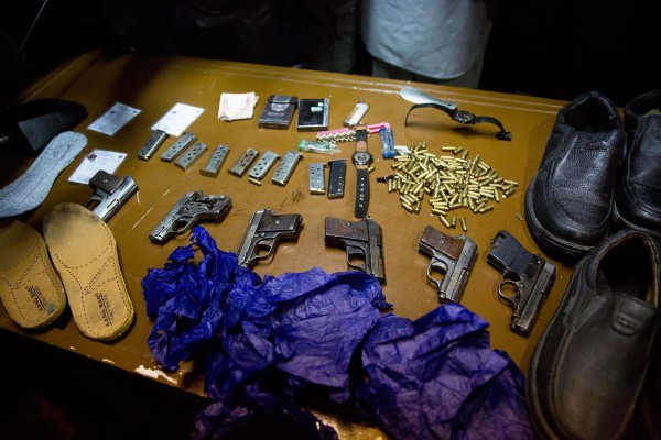 Image: Afghanistan's intelligence service displays some of the weapons and belongings of attackers on the Serena Hotel