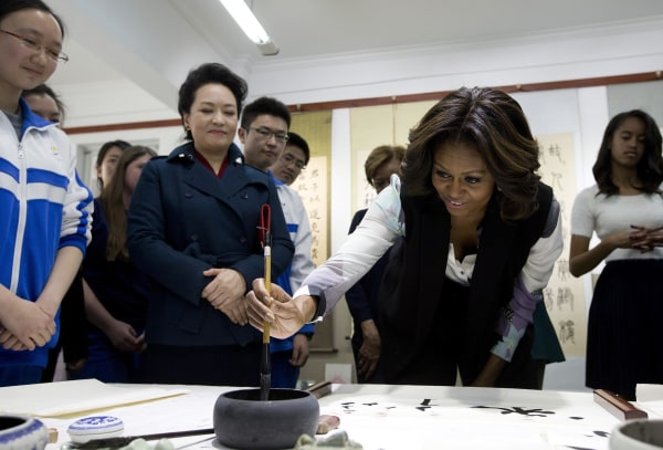 Image: First Lady Michelle Obama tries to write Chinese words with a brush