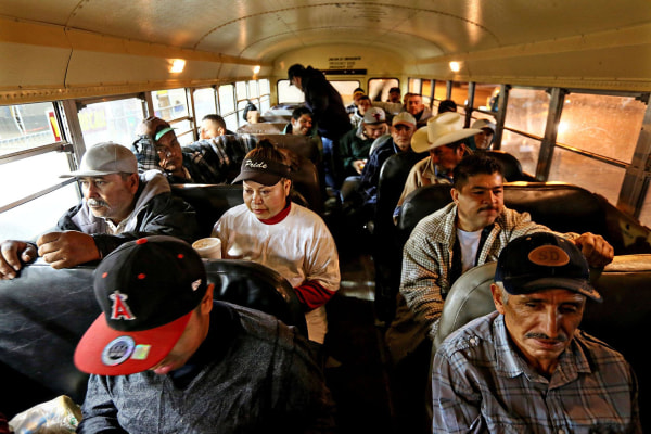 Image: Mexican agricultural workers are bussed to U.S. fields